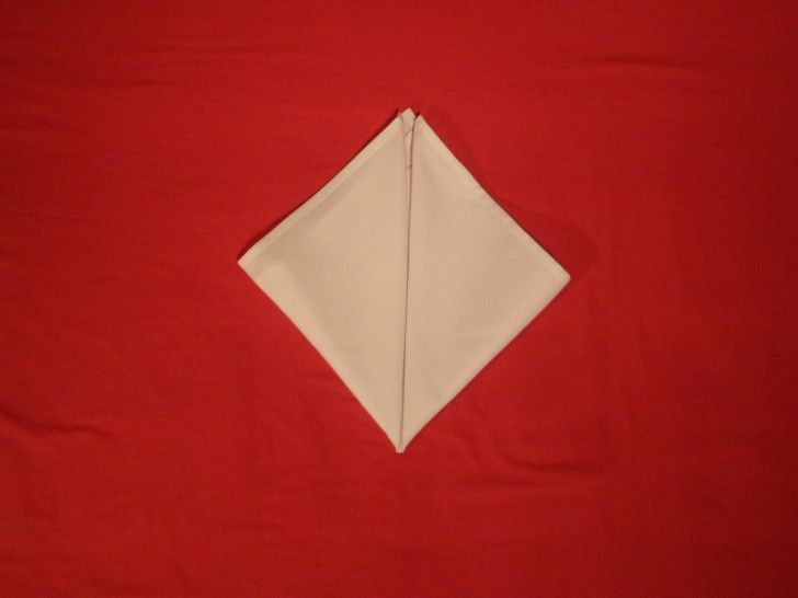 Napkin Origami The Cone Fold Step Five fold the opposite corner up tot he top so you have a diamond in front of you.