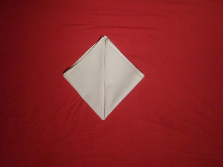Fancy Napkin Folding Techniques   Rosebud Fold Step Five fold the left corner up to the centre making the napkin look like a diamond.