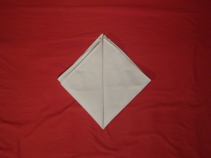 How To Fold Napkins The Crown Fold Step Four Copy the same fold as the previous step this time with the left corner.