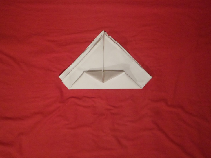 How To Fold Napkins The Crown Fold Step Six From the fold you just made take the point and fold it back on its self so its just touching the bottom. You may find it helps to use an iron if the napkin wont stay.
