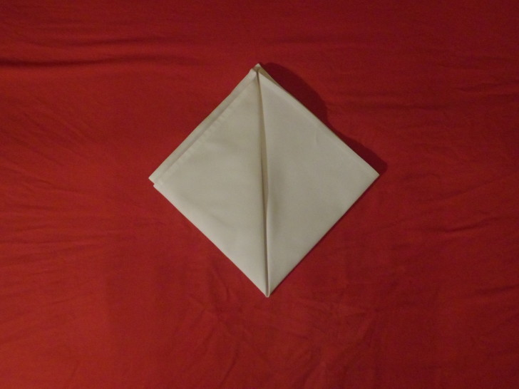 Folded Napkin Pyramid Fold Step Five Repeat the same action as the previous but with the bottom left corner creating a diamond.